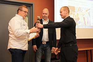 Henry Pohjolainen vastaanotti yhdestä puustä veistetyn Unski-patsaan liiton puheenjohtaja Hannu Herralalta ja asiamies Ville Reinikaiselta